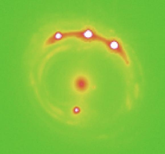 El cuásar RXJ 1131−1231 distorisonado por efecto de lente gravitatoria de una galaxia más cercana (University of Oklahoma).