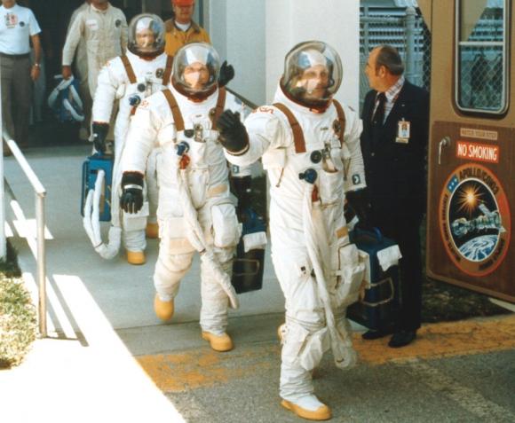 La tripulación de la misión Apolo-Soyuz (ASTP) de 1975 parte a la rampa con el gusano en las escafandras (NASA).