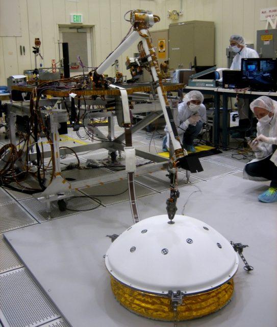 El brazo robot de InSight colocando el instrumento SEIS en la superficie (NASA).
